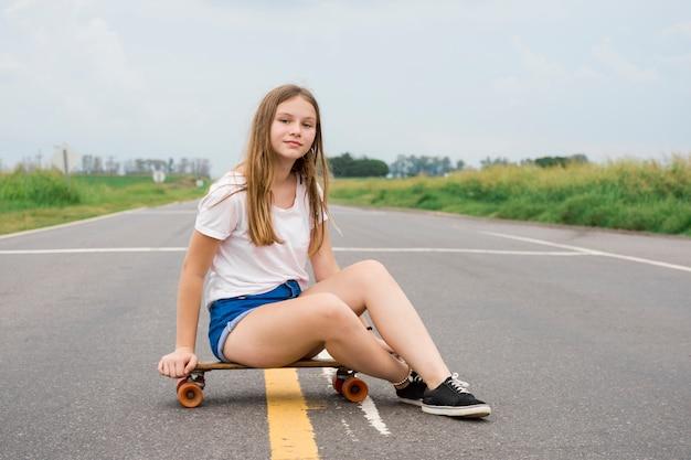 Modern attractive pretty girl sitting on skateboard on empty road Free Photo