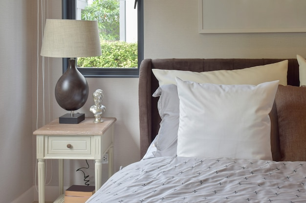 Modern bedroom interior with white and brown pillow on bed and decorative table lamp Premium Photo