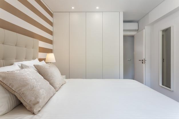 Современная спальня с подушками и кроватью для туристов. Premium Фотографии