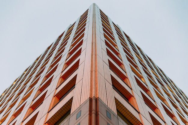 Modern building shot from below with clear sky in background in the evening Premium Photo