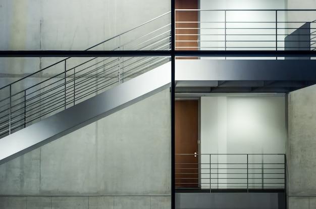 Edificio moderno con finestre in vetro e scale sotto le luci Foto Gratuite