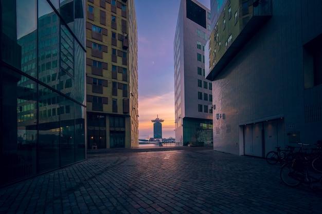 Современные здания со стеклянными окнами под пасмурным небом во время заката вечером Бесплатные Фотографии