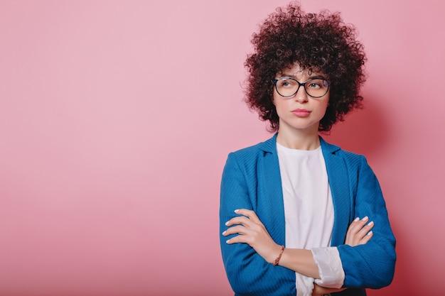 현대 비즈니스 여자는 파란색 재킷을 입고 불만족스러운 감정과 분홍색에 안경 포즈를 착용 무료 사진
