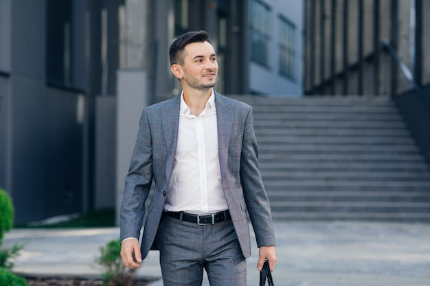 Modern businessman. confident young man in suit looking away while standing outdoors with cityscape in the background. handsome confident businessman portrait. Premium Photo