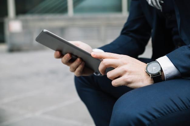 Modern businessman using device outdoors Free Photo