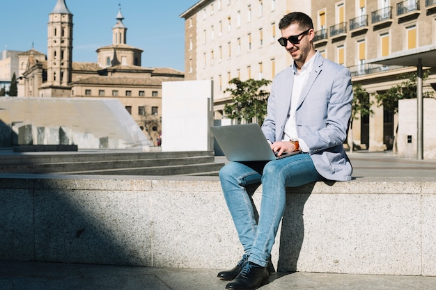 Modern businessman using laptop outdoors Free Photo