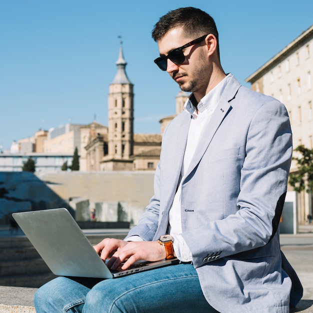 Modern businessman using laptop outdoors Free Photo