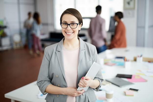 Современная деловая женщина позирует в офисе Premium Фотографии
