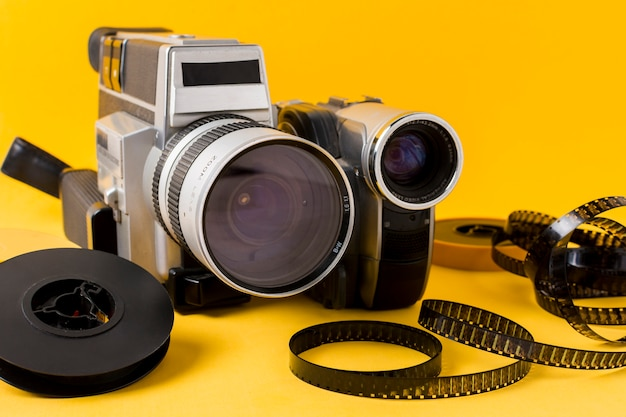Modern camera; film reel and film strips on yellow background Free Photo
