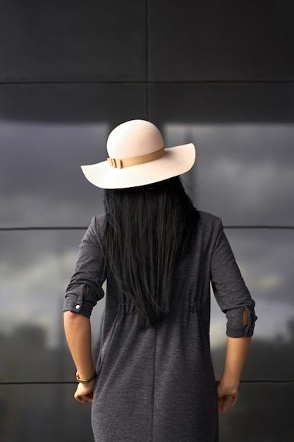 Modern collection. brunette girl wearing stylish grey dress and fashionable hat. model in trendy outfit posing on grey wall background. view from back. Premium Photo