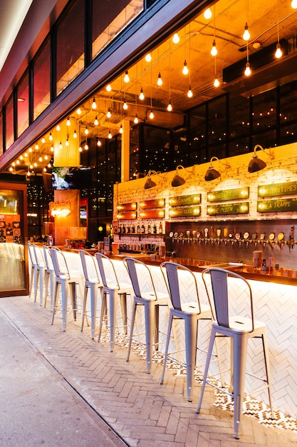 Modern decorated beer tap counter bar with empty seats in evening. Premium Photo