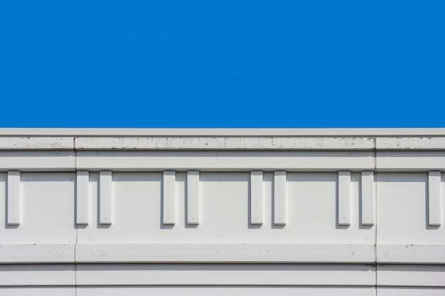 Modern design top part of high building wall with clear blue sky background. Premium Photo