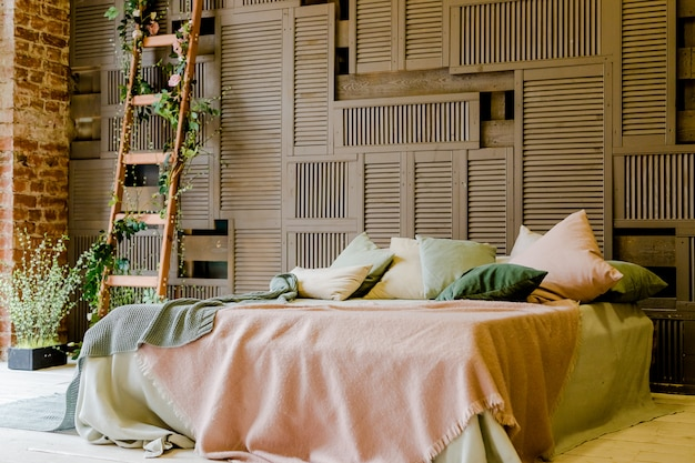 Modern double bed standing against wooden wall.interior with green and pink cozy pillows.stylish bedroom with cozy king size bed. loft style Premium Photo