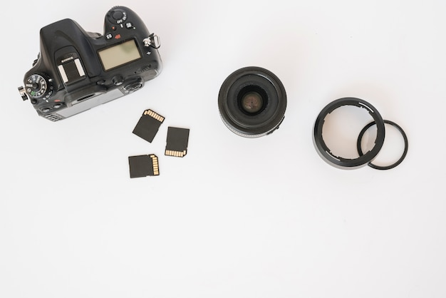 Modern dslr camera; memory cards and camera lens with extension rings on white backdrop Free Photo