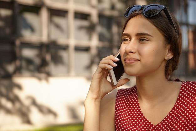 現代の電子ガジェット、人、コミュニケーションの概念。友人との素敵な会話をしながら、携帯電話で話している点線の赤いドレスを着た美しい日焼けしたヨーロッパの女性のクローズアップショット 無料写真