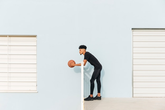 Modern ethnic standing with basketball Free Photo
