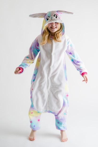 Modern fashion - красивая блондинка позирует на белом фоне в пижаме кигуруми, в костюме зайчика Premium Фотографии