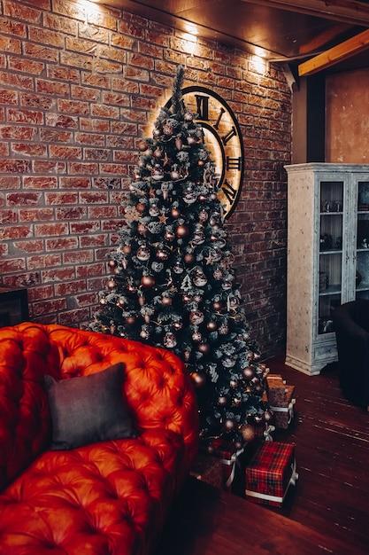 쿠션이있는 현대적인 세련된 빨간색 가죽 소파. 자른 크리스마스 트리. 벽돌 벽. 로프트 디자인. 무료 사진