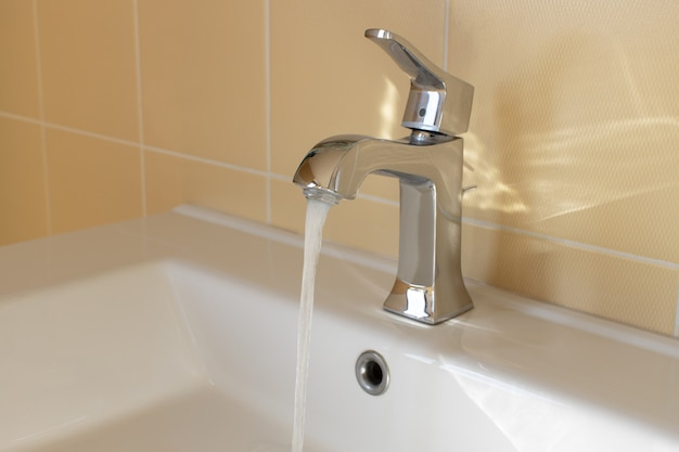 Modern faucet in yellow bathroom with running water, close up, side view. concept hygiene, house cleaning, water saving, supply problems, reducing use, conscious consumption. horizontal. Premium Photo