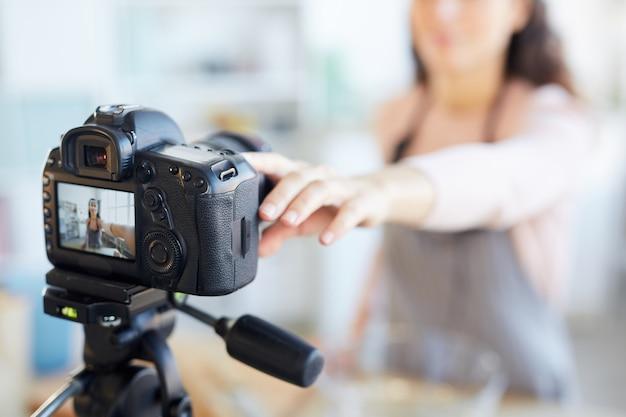 Modern female food blogger setting her camera before shooting start, horizontal camera in focus shot Premium Photo