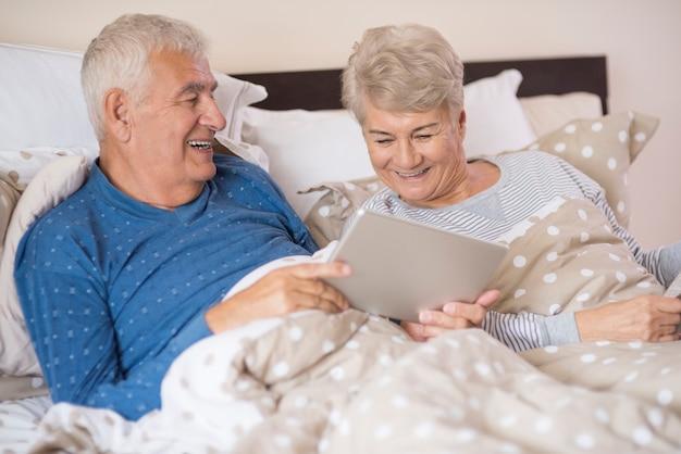 Nonni moderni che riposano nella camera da letto Foto Gratuite