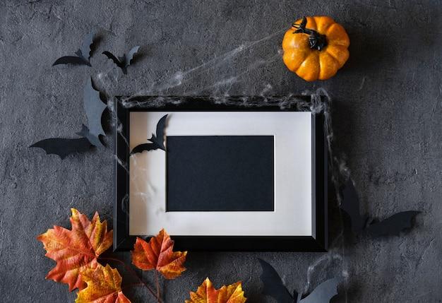 Modern halloween background with pumpkins, bats and black frame on dark background Premium Photo