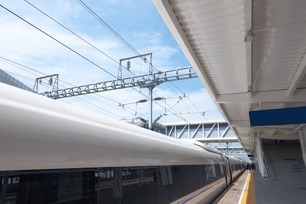 Modern high speed train at the railway station with motion blur effect Premium Photo