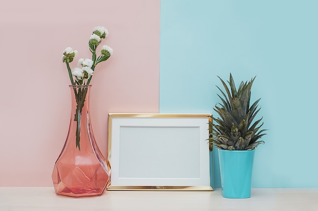 Modern home decor mock up with gold photo frame, vase and tropical plant on pink blue back Premium Photo