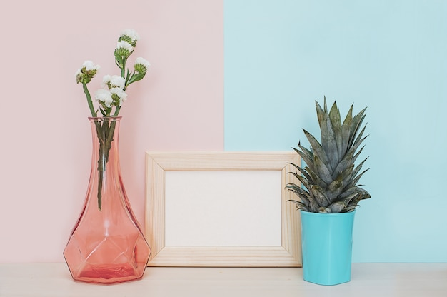 Modern home decor mock up with wooden photo frame, vase and tropical plant on pink blue ba Premium Photo