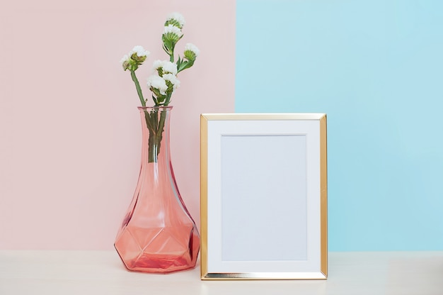 Modern home decor with gold blank photo frame, vase and tropical plant on pink blue backgr Premium Photo