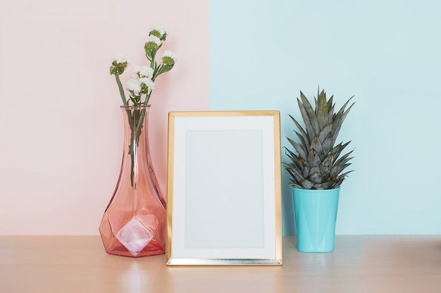 Modern home decor with gold mock up photo frame, vase and tropical plant on pink blue back Premium Photo