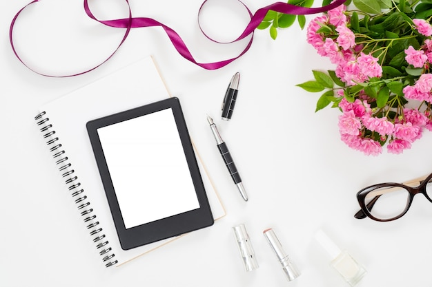 Modern home office desk workspace with blank screen tablet e-book, feminine accessories, glasses, paper notebook, bouquet of pink rose flowers Premium Photo