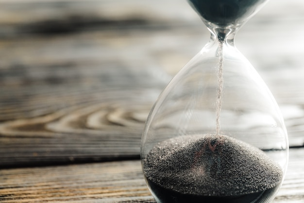 Modern hourglass on wooden surface Premium Photo