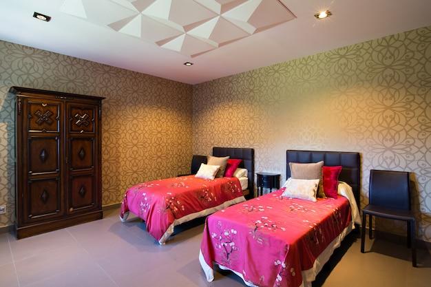 Современная комната дома, с обоями и двумя односпальными кроватями с фуксия одеяла. декоративный потолок. Premium Фотографии