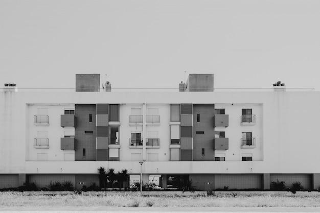 식물과 나무 앞에 흑백 발코니와 창문이있는 현대 주택 무료 사진