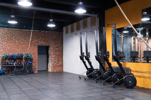 Modern interior of fitness gym with rowing machines and sport equipment Premium Photo