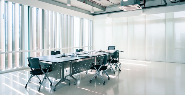 Modern interior meeting room of marketing office with evening sunset, empty large loft style conference space with chairs and tables furniture and clean glass windows Premium Photo