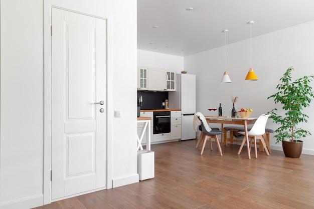 Современный интерьер кухни, белая стена, деревянные стулья, зеленый цветок в горшке. концептуальный скандинавский дизайн Premium Фотографии