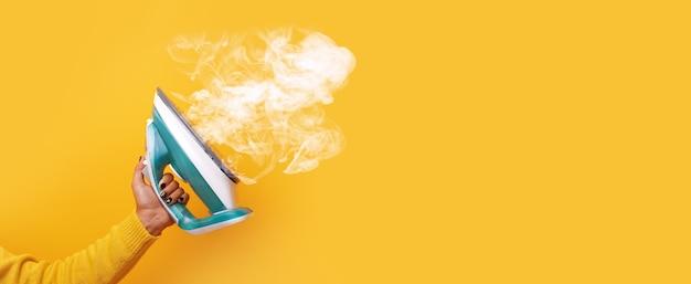 黄色の背景、パノラマのモックアップ画像の上に蒸気を手にモダンな鉄 Premium写真