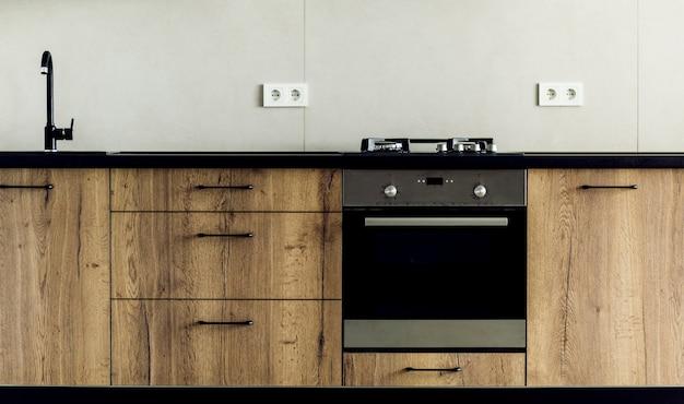 Современная кухня, крупный план, газовая плита с кастрюлей, белый и серый минималистичный дизайн интерьера. Premium Фотографии