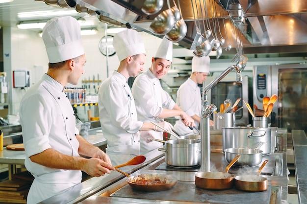 モダンなキッチン。料理人はレストランやホテルのキッチンのストーブで食事を準備します。台所の火。 Premium写真