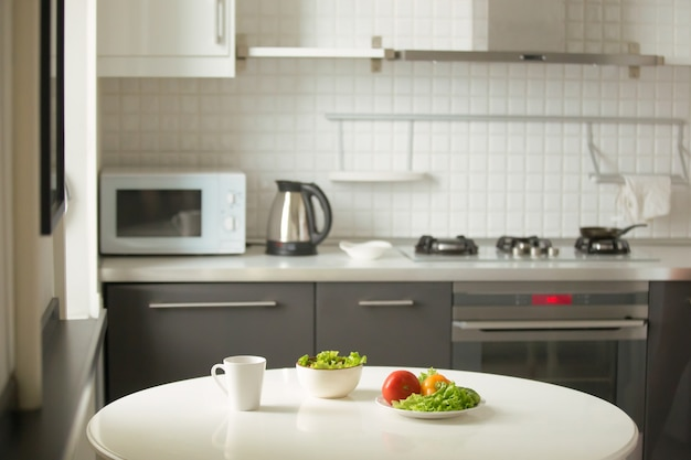 Modern kitchen, a white table, mug and green salad Free Photo