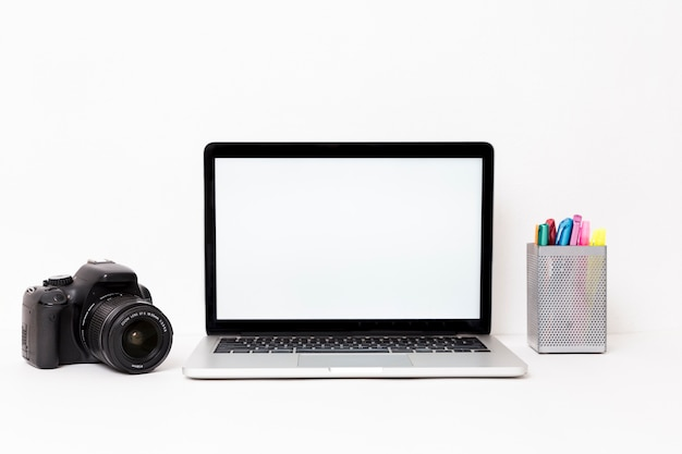 Modern laptop and camera on white background Free Photo