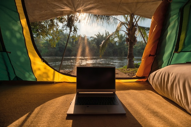Modern laptop open and put down inside a camping tent in natural park at sunset