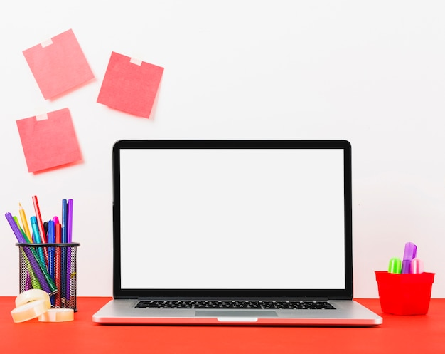 Modern laptop with blank adhesive notes on white wall Free Photo