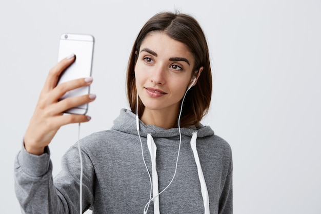 Современный образ жизни. крупным планом красивая молодая брюнетка кавказская девушка в случайных балахон, разговаривая с парнем с видео на смартфоне, в наушниках Бесплатные Фотографии