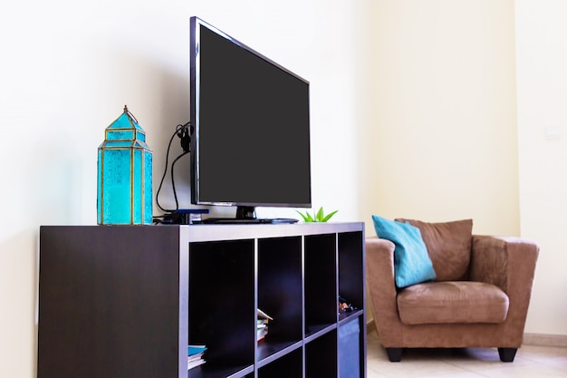 Современный интерьер гостиной, умный телевизор, велюровое кресло, подушки. полка, арабский фонарь. макет. концепт дизайна. Premium Фотографии