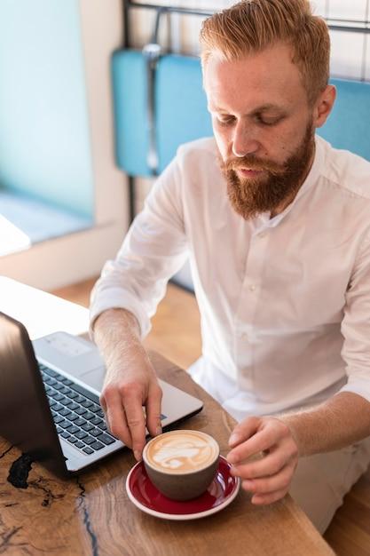 Uomo moderno che mette la sua tazza di caffè accanto al suo laptop Foto Gratuite