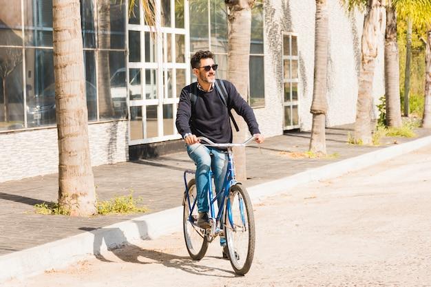 Современный человек в темных очках катается на велосипеде по улице Бесплатные Фотографии