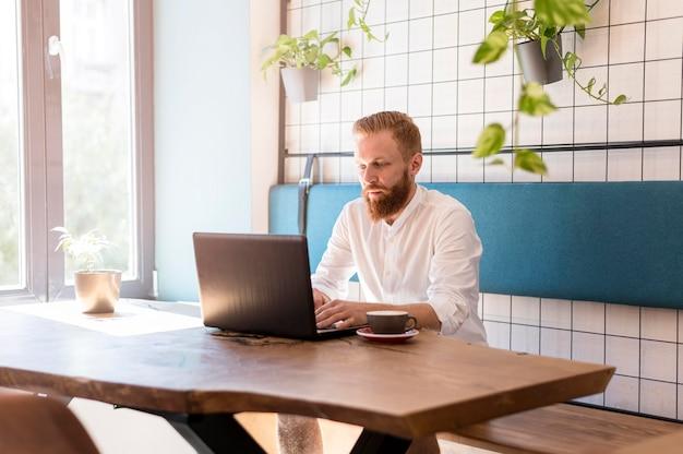 Uomo moderno che lavora al suo computer portatile Foto Gratuite